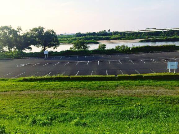 渡橋の下に広がる矢作川沿いの駐車場